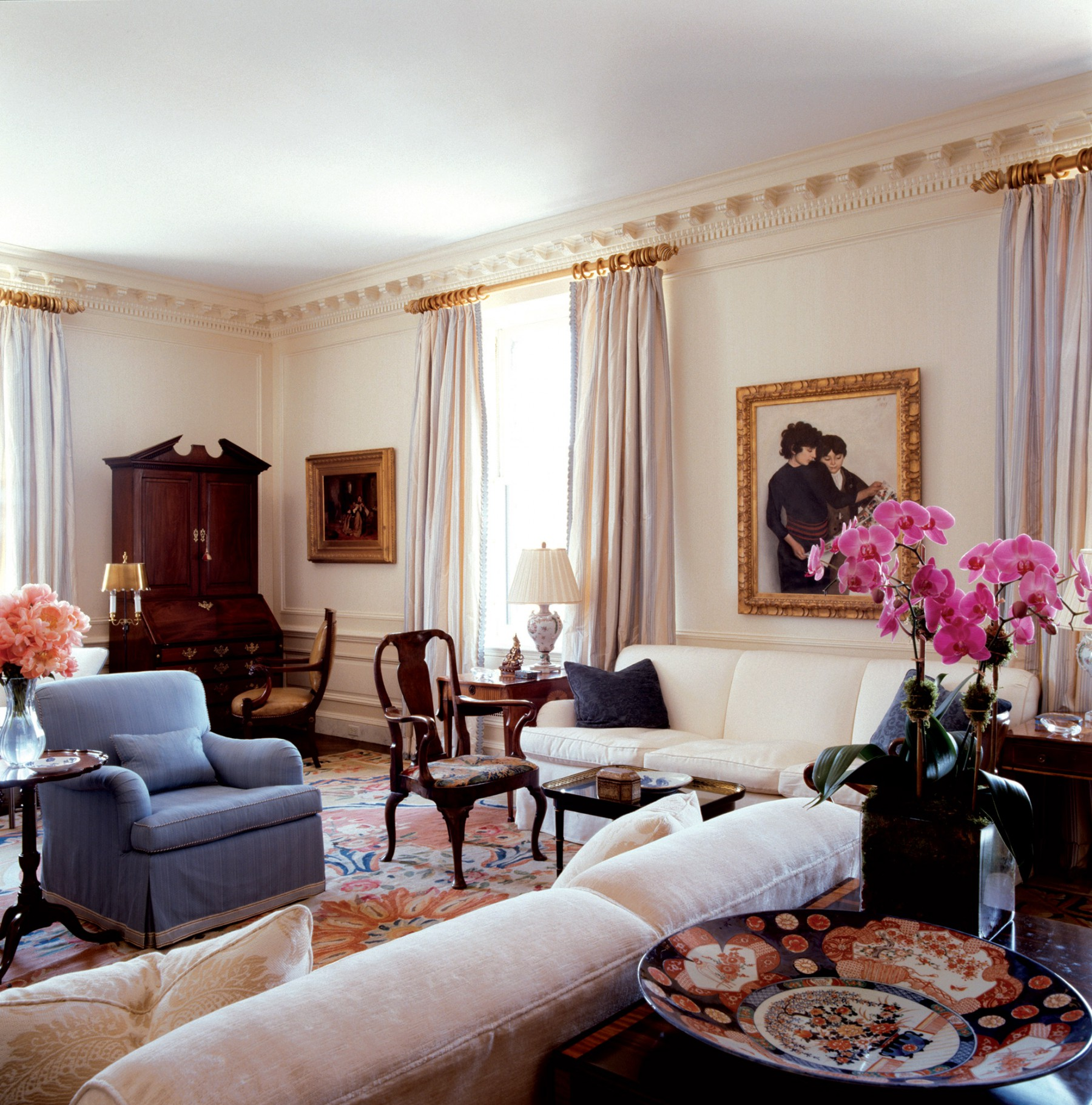 bright traditional living room with gold frame paintings hidden amenities and cove molding